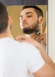 Man shaving the beard with a razor Stock Photos