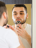 Man shaving the beard with a razor Stock Images