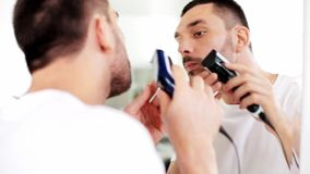 Man shaving beard with trimmer at bathroom stock video