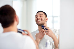 Man shaving beard with trimmer at bathroom Stock Images