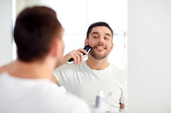 Man shaving beard with trimmer at bathroom Royalty Free Stock Images