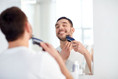 Man shaving beard with trimmer at bathroom Royalty Free Stock Photos