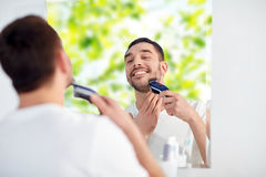 Man shaving beard with trimmer at bathroom Stock Photography