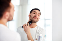 Man shaving beard with trimmer at bathroom Royalty Free Stock Image