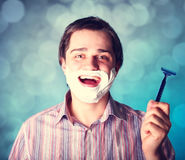 Man shaving  on blue background Royalty Free Stock Image
