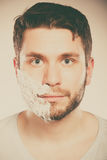 Man with shaving cream foam on half of face. Royalty Free Stock Photos