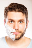 Man with shaving cream foam on half of face. Stock Image