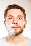 Man with shaving cream foam on half of face. Stock Photos