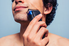 Man shaving with electric razor Royalty Free Stock Photos