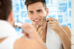 Man shaving with electric shaver. Reflection of young man in mirror shaving with electric shaver Stock Photo
