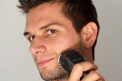 Man shaving face with electric razor. Man shaving face and smiling with electric razor Stock Photo