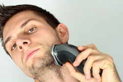 Man shaving face with electric razor. Man shaving beard in face with electric razor Stock Photo