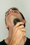 Man shaving face with electric razor. Man shaving beard in face with electric razor Stock Photography