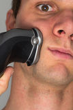Man shaving face with electric razor. Man shaving beard in face with electric razor Royalty Free Stock Photos