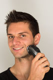 Man shaving face with electric razor. And smiline Stock Photography