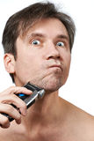 Man shaving face with electric razor Stock Image