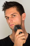 Man shaving face with electric shaver. Man shaving face with electric razor Royalty Free Stock Photos