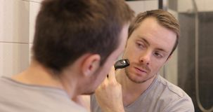 Man shaving face with trimmer looking at mirror in the bathroom. Man shaving face with trimmer looking at mirror in a bathroom stock footage