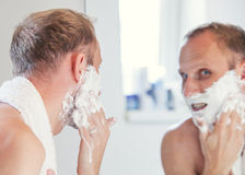 Man with shaving foam on face Royalty Free Stock Image