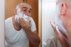 Man shaving. In front a mirror royalty free stock photos