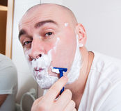 Man shaving. In front a mirror stock photography