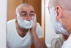 Man shaving. In front a mirror stock images