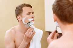 Man shaving in front of mirror. With caution. Topless handsome man shaving in front of mirror and holding towel on his shoulder Royalty Free Stock Images