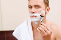 Man shaving in front of mirror Stock Images