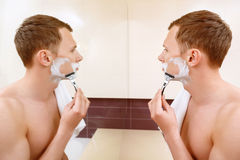 Man shaving in front of mirror Royalty Free Stock Photography
