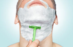 Man is shaving with green razor Stock Images