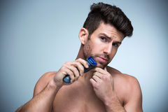 Man shaving. Handsome Man shaving with electric razor stock image