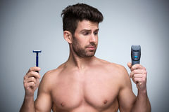 Man shaving. Handsome Man shaving with electric razor royalty free stock image