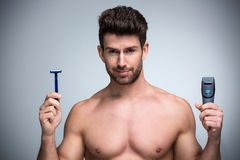 Man shaving. Handsome Man shaving with electric razor royalty free stock photos