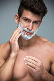 Man shaving. Handsome Man shaving over grey background royalty free stock photography
