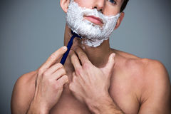 Man shaving. Handsome Man shaving over grey background royalty free stock image