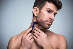 Man shaving. Handsome Man shaving over grey background stock image