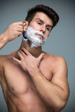 Man shaving. Handsome Man shaving over grey background stock photography