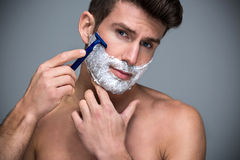 Man shaving. Handsome Man shaving with razor stock images