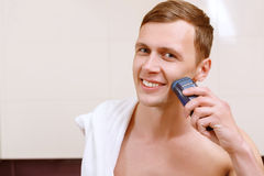 Man shaving with help of electric razor Stock Image