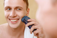 Man shaving with help of electric razor Royalty Free Stock Image