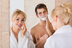 Man Shaving And Her Wife Cleaning Her Face. Portrait Of A Man Shaving And Her Wife Cleaning Her Face In Mirror At Bathroom stock image