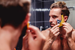 Man shaving his beard in the bathroom. Hipster man shaving his beard in the bathroom royalty free stock image