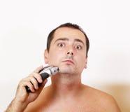 Man shaving his beard with an electric razor. Man shaving his beard off with an electric razor Royalty Free Stock Image