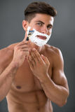 Man shaving his beard. Handsome man shaving his beard with lot of shave foam on face Royalty Free Stock Image