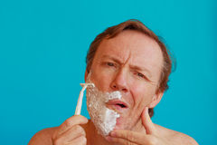 A man shaving his beard with  razor -blade. A man tilts his face and stretches the skin with your hand to shave his beard with  razor-blade Royalty Free Stock Image