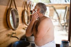 Man shaving his beard with razor in cottage. During safari vacation Royalty Free Stock Photo