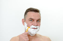 Man shaving his beard with a razor and lather. Middle-aged man shaving his beard with a razor and lather from shaving cream covering his face, isolated on white Stock Photos