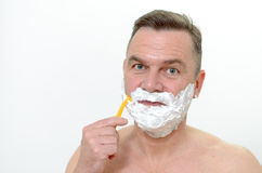 Man shaving his beard with a razor and lather. Middle-aged man shaving his beard with a razor and lather from shaving cream covering his face, isolated on white Royalty Free Stock Photography