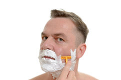 Man shaving his beard with a razor and lather. Middle-aged man shaving his beard with a razor and lather from shaving cream covering his face, isolated on white Royalty Free Stock Photo