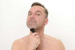 Man shaving his beard with a razor and lather. Middle-aged man shaving his beard with a razor, isolated on white Royalty Free Stock Image